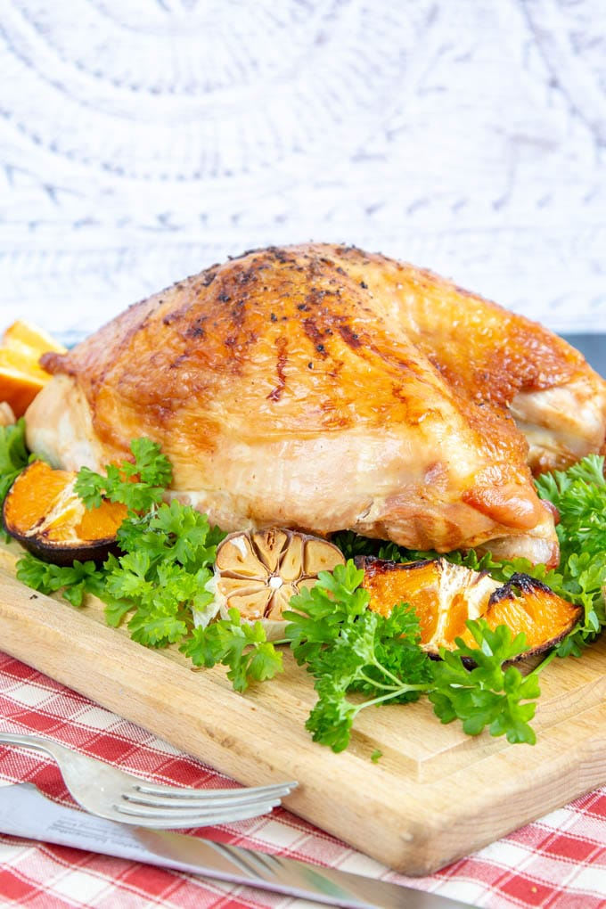 A golden brown roast turkey crown on a wooden board with parsley, roast orange and garlic.