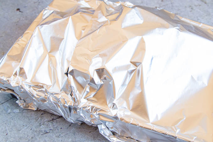 A turkey crown on a roasting tray, covered with foil.