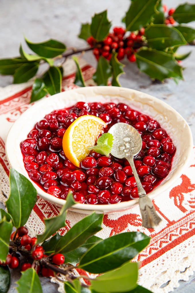 A bowl full of cranberry sauce, garnished with mint and a slice of orange, surrounded with holly.