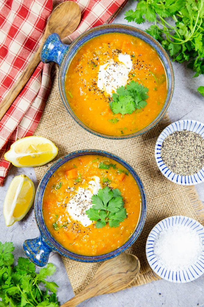 Two bowls of spicy carrot lentil soup from above, with vibrant green parsley surrounding.