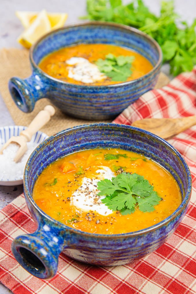 Two blue bowls filled with bright orange carrot and lentil soup, garnished with yoghurt and parsley