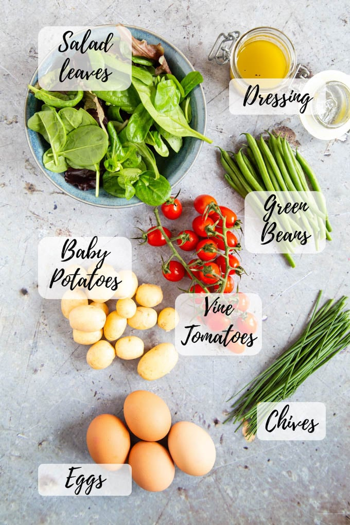 A top down picture of the ingredients for egg and potato salad, with vibrant greens and reds.
