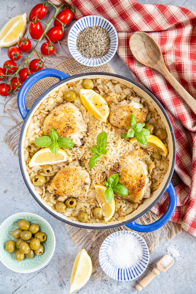 Top down picture of Greek chicken one pot, surrounded by olives, salt, pepper and tomatoes