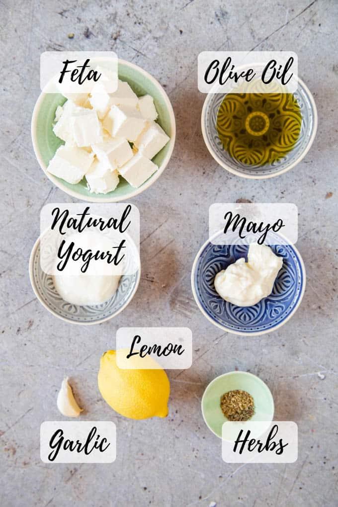 The ingredients for whipped feta dip - feta, olive oil, yogurt, mayo, lemon, garlic & herbs.