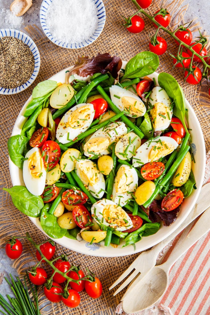 A top down picture of a salad of egg, potato, green beans, salad leaves and cherry tomatoes, garnished with chives.