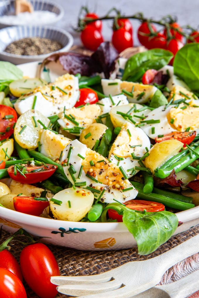 Egg and potato salad, with tomatoes, beans, and salad leaves fill the frame.