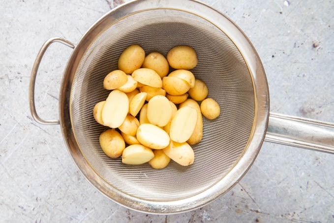Steamed new potatoes draining in a sieve.