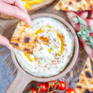 A top down picture of a slice of flatbread dipped in a flat bowl of feta dip.