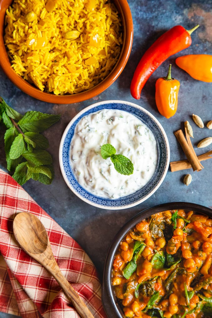 Top down picture of a bowl of cucumber raita on a dark background, surrounded by chillis, pilaf rice and curry.