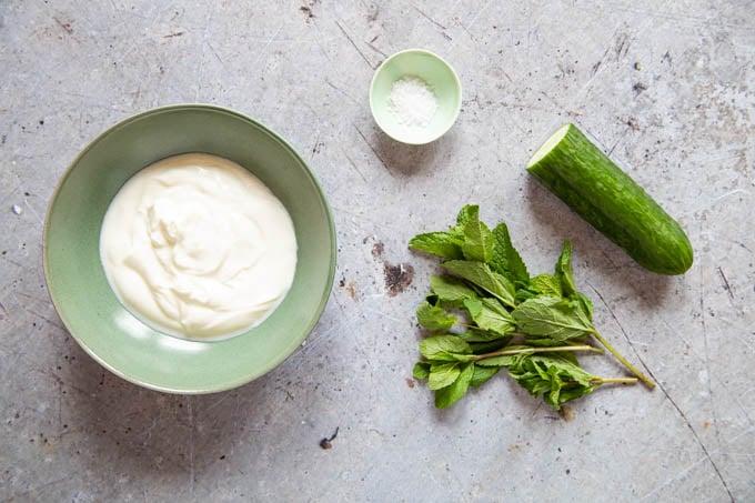Ingredients for cucumber raita - cucumber, yogurt, mint, salt.