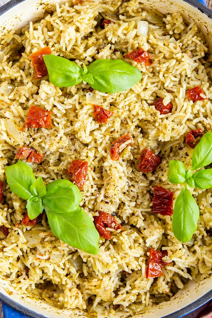 Close uptop down picture of golden yellow Italian rice garnished with bright green basil leaves.