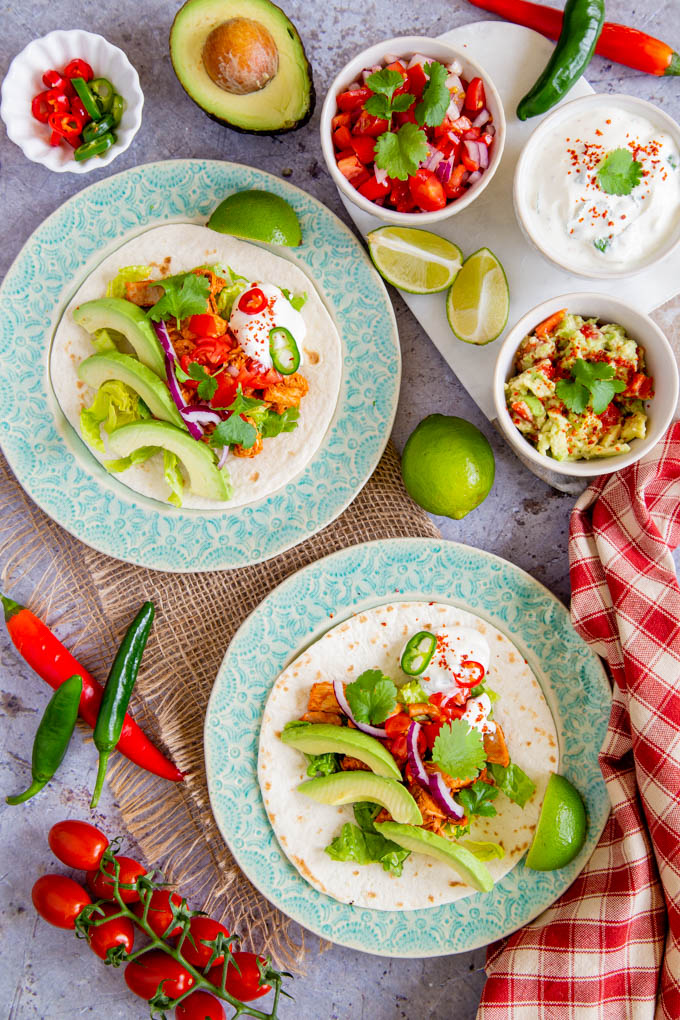 A top down picture of two plates, each holding a yet to be rolled chicken taco. Sour cream, guacamole, avocados, chillies, tomatoes and relish garnishes and extras surround the plates.