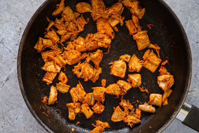 Pieces of spice covered chicken in a frying pan