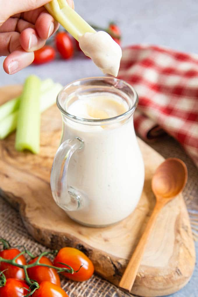 A hand holds a stick of celery above a glass jug of homemade salad cream. The celery has been dunked and has a big blob of thick dressing on the end.