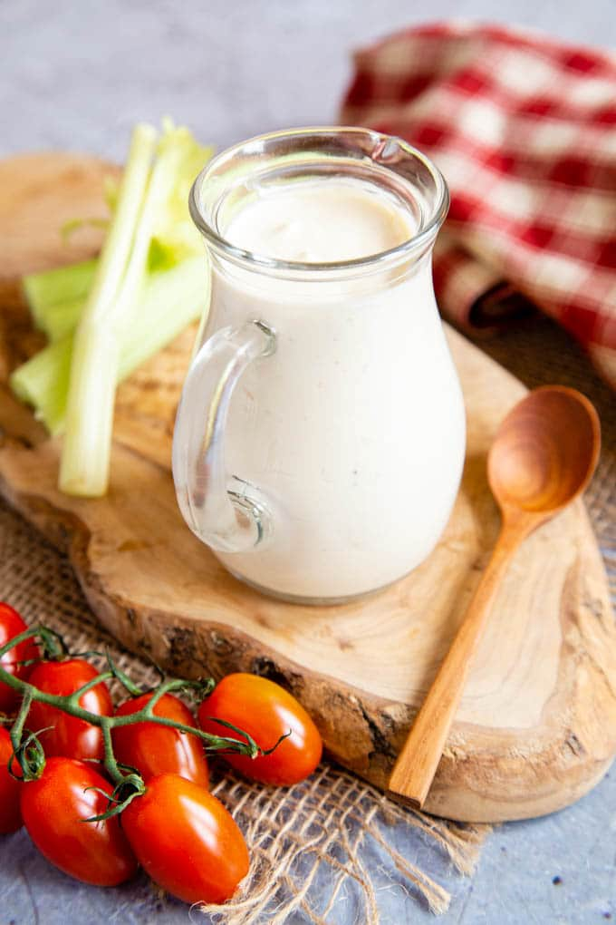 A glass jug of fresh salad cream standing on a wooden board