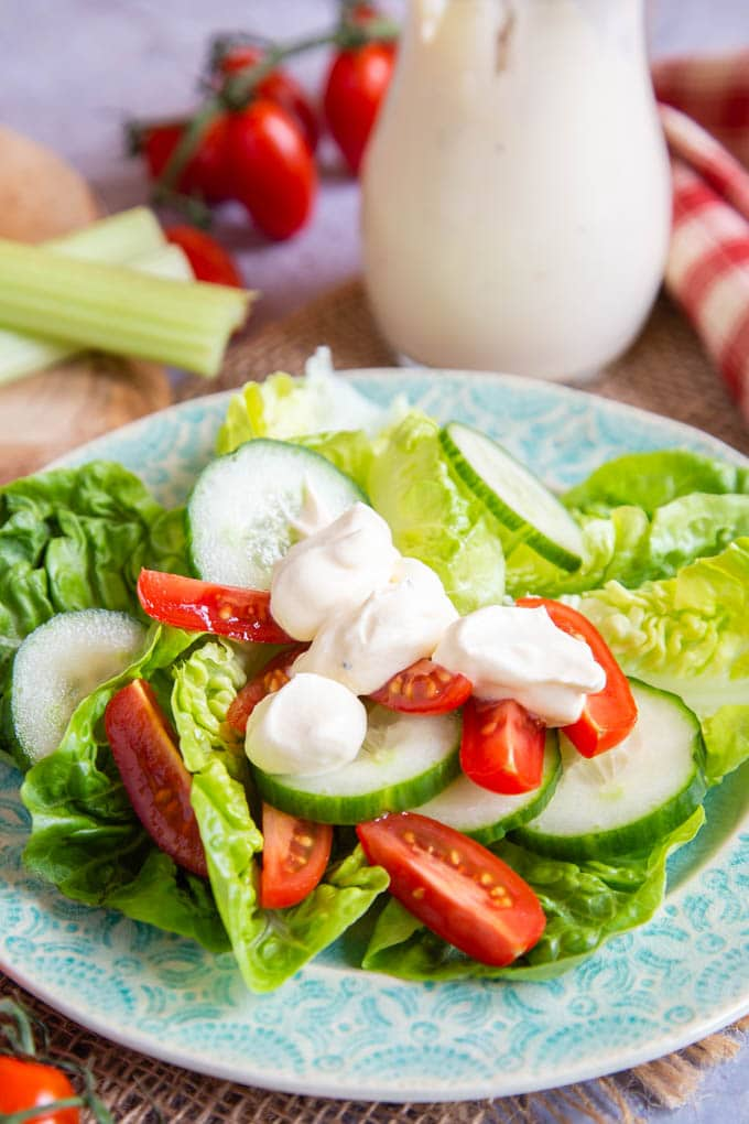 Big dollops of salad cream on a simple lettuce, tomato and cucumber salad, served on a green plate. A glass jug of more salad cream in the background.