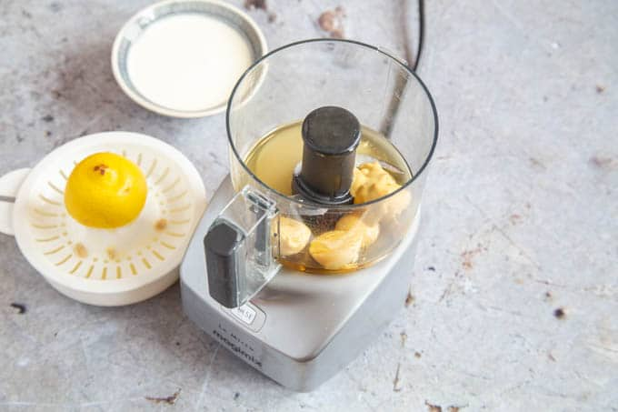 Mustard, egg yolks and lemon juice in a miniature blender, ready to blend.
