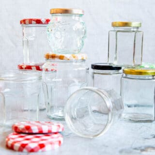 9 empty clean jam jars, 2 with lids off, stacked up 2 high.