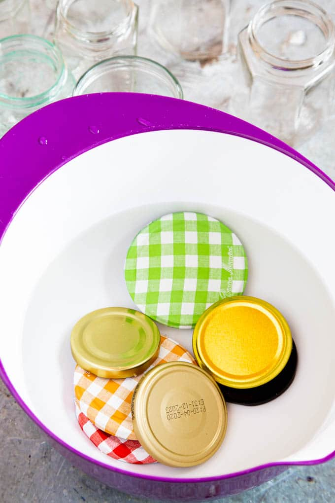 Jam jar lids in a bowl covered with water. The water was poured in boiling from the kettle to sterilize the lids.