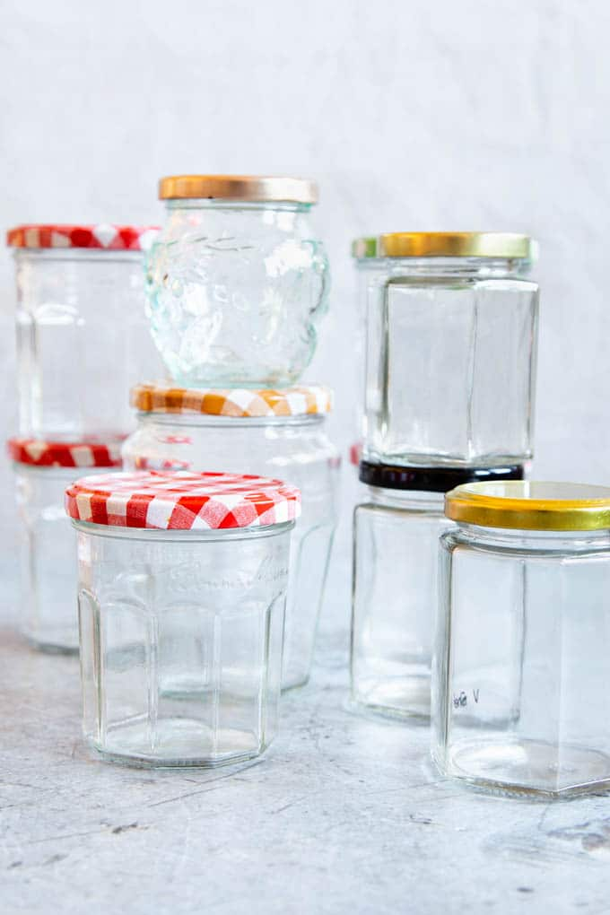 Different shapes of empty jam jars with lids, clean, ready to sterilize and fill with jam.