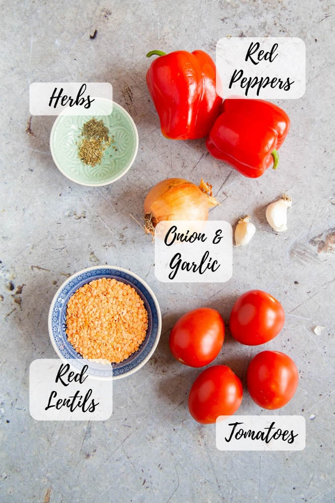 Annotated picture of ingredients for red pepper tomato and red lentil soup; red peppers, herbs, onion and garlic, red lentils, tomatoes.