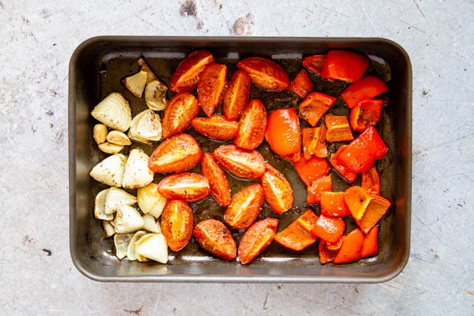 Onions, tomatoes and red peppers after roasting, in a roasting pan.