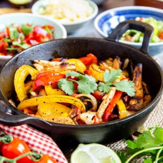 Close up on cooked fajita filling, surrounded by toppings.