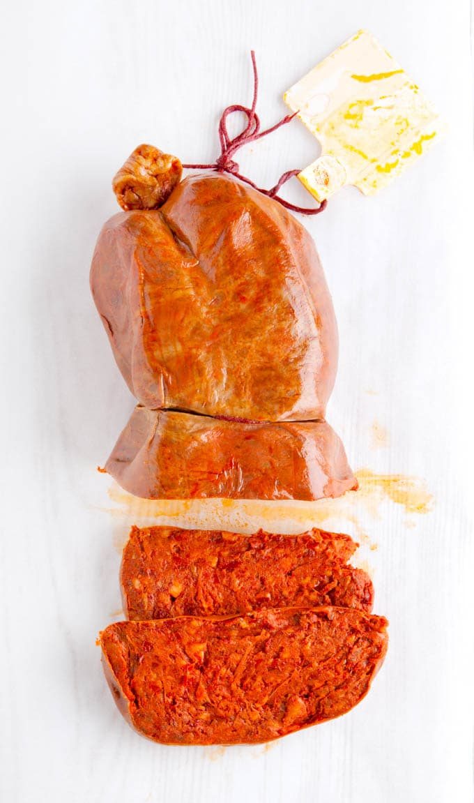 Top down view of a sliced nduja sausage on a white background