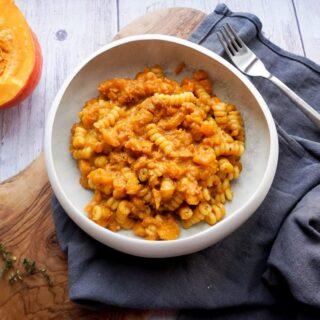 A bowl of pasta swirls in orange pumpkin sauce with nduja