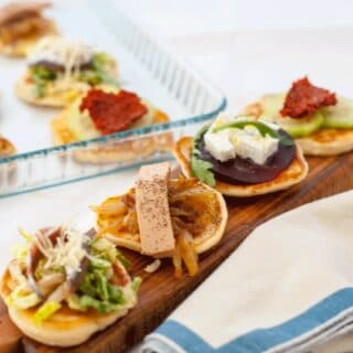 Four blinis on a wooden board with different toppings
