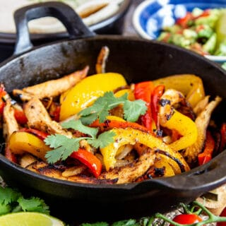 A close up of a hot cast iron skillet filled with sizzling chicken, onion and pepper fajita filling.