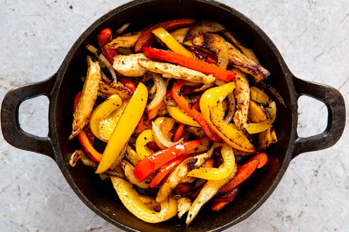 A top down picture of chicken, bell peppers, and onion cooked until slightly charred, served in a cast iron skillet.