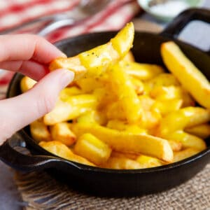 Close up of cheesy chips being taken from a serving dish full.