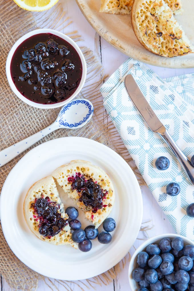 A flat layout of blueberry jam in a small dish, and a toasted crumpet with butter and jam spread on top. Fresh blueberries, another crumpet, knives, and jam spoons surround.