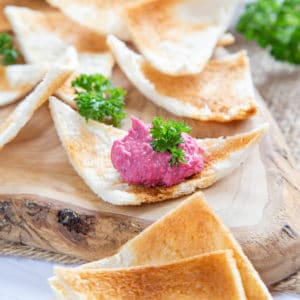 A close up of slices melba toast on a rustic wooden board. A serving of pink dip is on one slice, garnished with parsley.