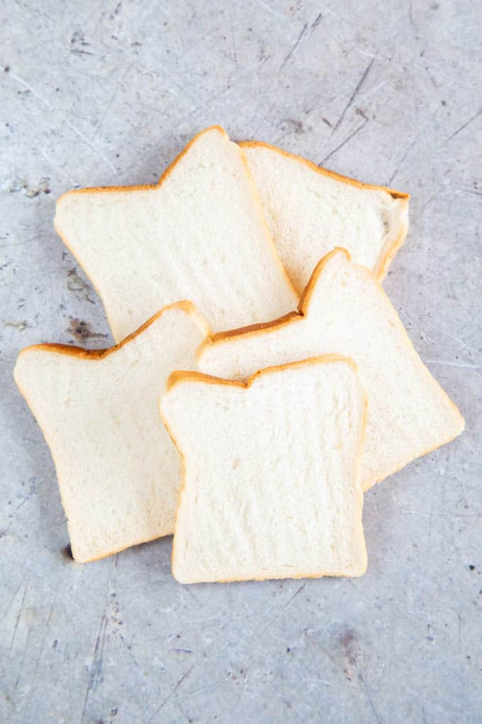 Slices of white sandwich bread, ready for toasting.