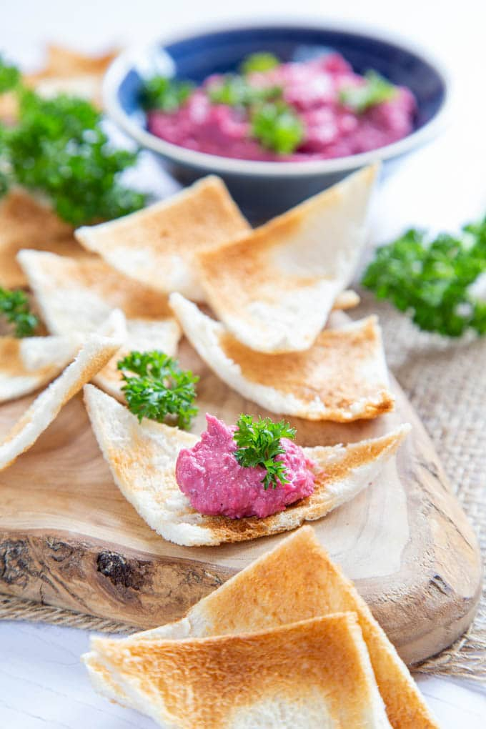 A close up of slices of crisp brown curved melba toast, with a serving of pink beetroot dip on one slice.