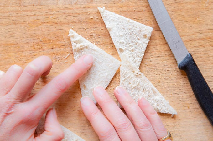 Making melba toast - brushing the bread crumb off the sliced open toast.
