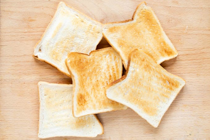 Making melba toast - five slices of white bread that have been toasted golden brown, roughly arranged on a wooden board.