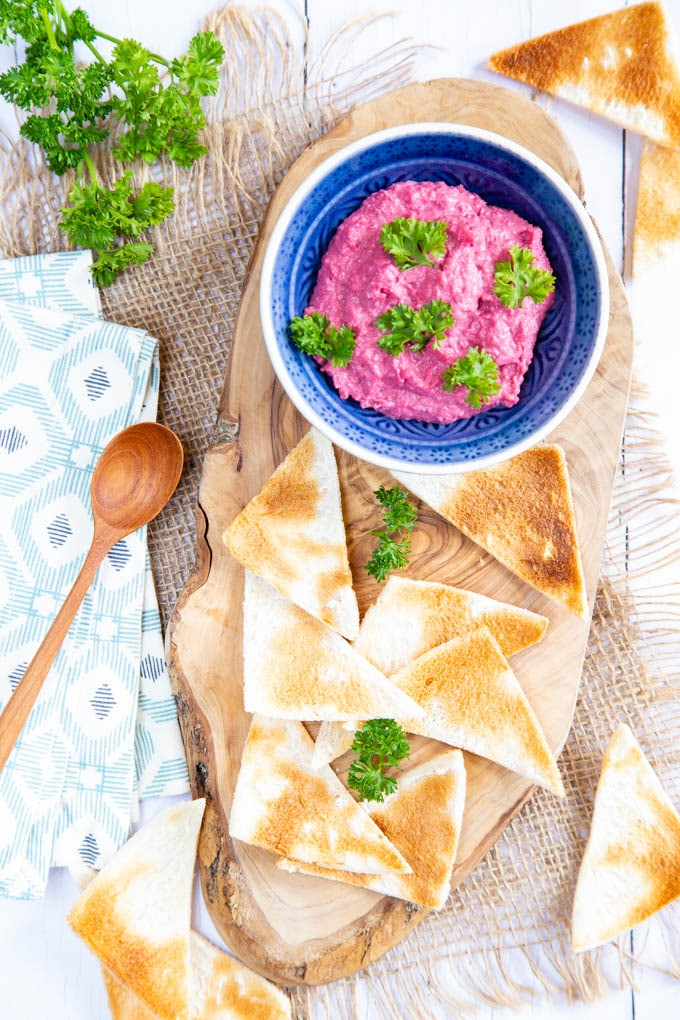 A top down picture of slices of melba toast on a rustic wooden board. Next to the toast is a small blue dish of pink beetroot dip.