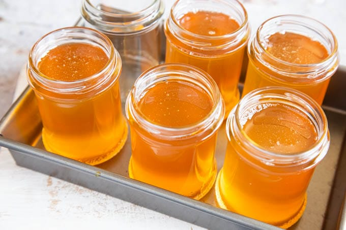 Five out of six jam jars full of golden orange clear medlar jelly, ready for lids.