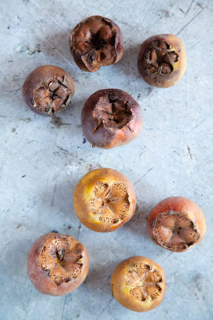 8 medlars, 4 pale & unbletted, 4 dark brown and bletted.