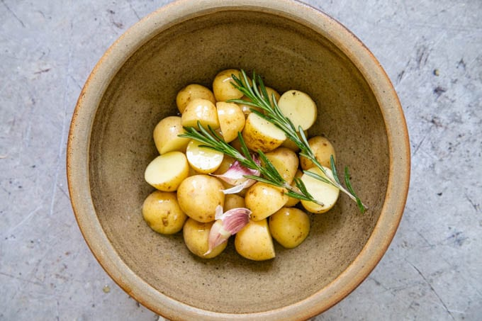 A bowl of baby potatoes dressed in oil with rosemary and garlic, ready to cook.