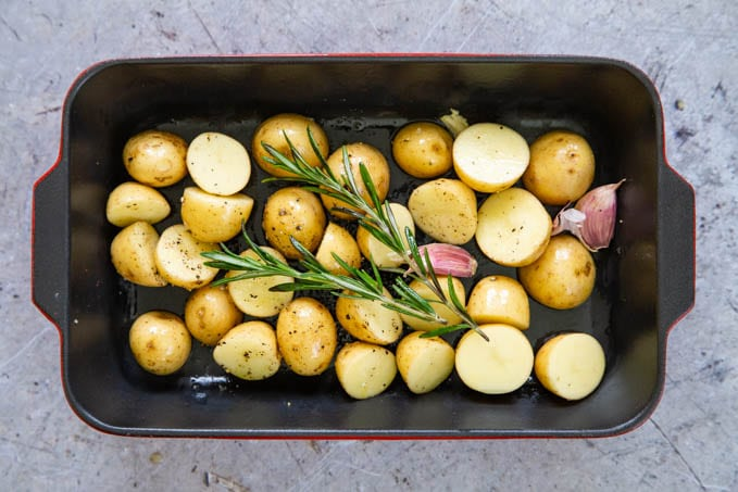 Baby potatoes with oil, garlic, seasoning and rosemary ready to cook.