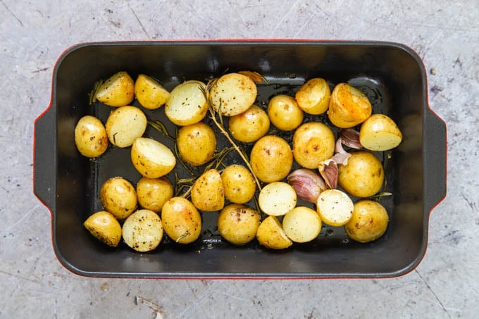 Cooked baby roast potatoes in a black rectangular dish, taken from above.