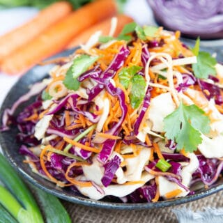 Close up of vibrant red cabbage, carrot and crispy white cabbage coleslaw.