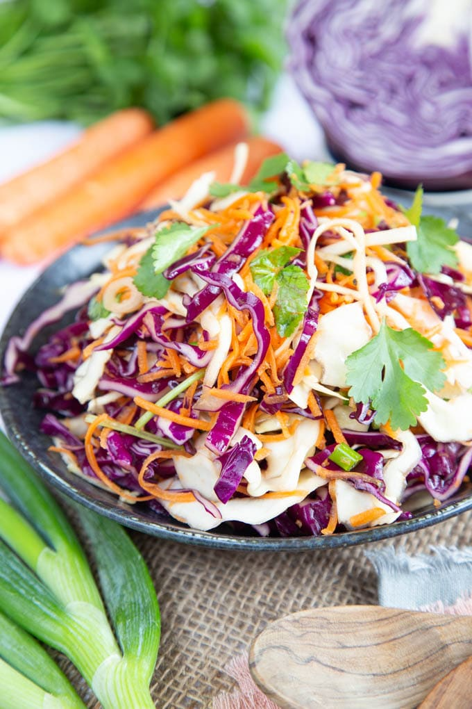 A shallow bowl of no-mayo slaw from red and white cabbage, grated carrot, and coriander leaves, in close-up.