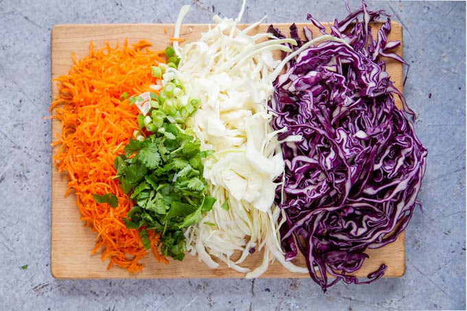 Sliced red and white cabbage, grated carrot and chopped coriander and spring onions for no-may slaw.