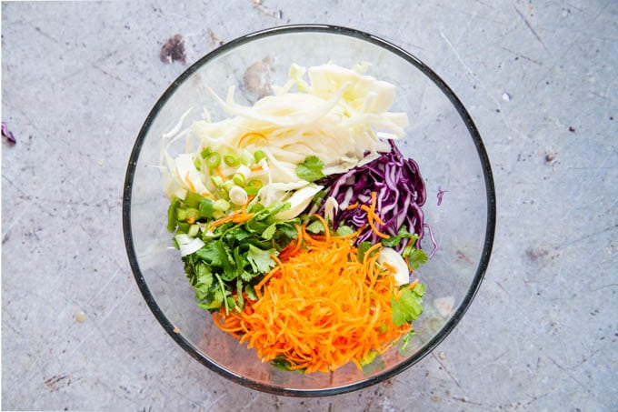 The salad ingredients for no-mayo slaw have been added to the bowl.