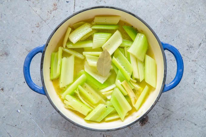 Fried celery pieces with stock added, ready to simmer and cook.
